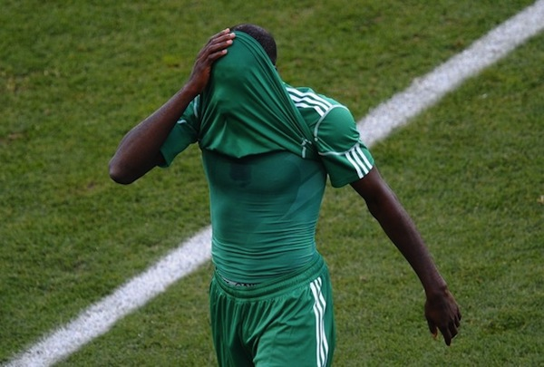 Nigeria's midfielder Sani Kaita hides his face after being handed a red card for kicking Greece's defender Vasilis Torosidis