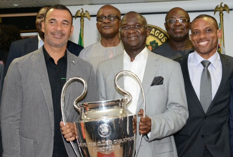 Governor Babatunde Raji Fashola carrying the UEFA Cup flanked by Ruud Gullit and Sunday Oliseh